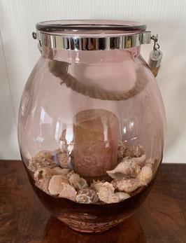 Glazen vaas met schelpen en kaars