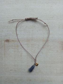 Cremefarbenes Textilarmband mit grauer Textiltroddel und kleinem goldfarbenem Herzanhänger