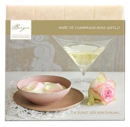 Marc de Champagne gefüllt 100 G - Weiße Schokolade mit 29 % Kakaoanteil, gefüllt mit einer cremig-eleganten Marc de Champagne-Canache und mit Rosenöl verfeinert. Bestreut mit Rosenblüten.