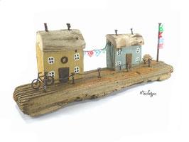 Treibholz -Häuser mit Wimpelkette, Fahnenmast, Fahrrad, Bank