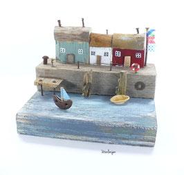Treibholz - Fischerhäuser auf Mole mit Wimpel, Segelboot