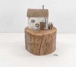 Treibholz - Haus mit Kaminholz auf Baumscheibe