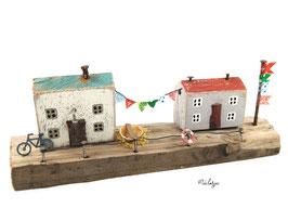Treibholz -Häuser mit Wimpelkette, Fahnenmast, Fahrrad, Boot