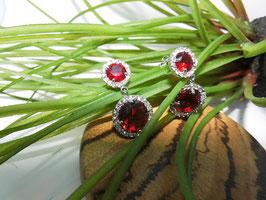 Edle Ohrhänger mit funkelndem roten Kristall