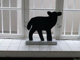 Schwarzes Lämmlein auf Granitsockel.