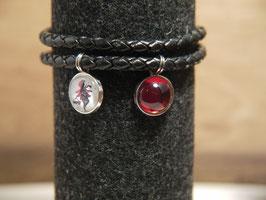 Rotkäppchen als Scherenschnitt mit einem roten Anhänger am geflochtenen schwarzen Lederarmband