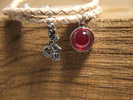 Rotkäppchen mit Figuren und rotem Anhänger am geflochtenen Lederarmband