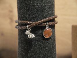 Das Armband für Hundefreunde, der kleine Hund mit einem Anhänger mit braunem Glas an einem braunen Lederband
