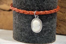 Bei dieser Gemme gibt es einen perlmuttfarbenen Grund mit weißer Silhouette an rotbraunen Lederarmband