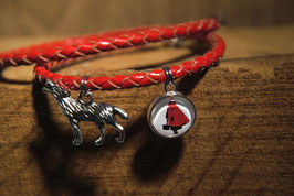 Rotkäppchen als Scherenschnitt mit rotem Mantel mit einem Wolf am geflochtenen rotem Lederband