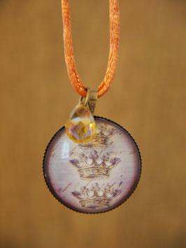 Anhänger mit drei Kronen und einem cognacfarbenen Glitztertropfen an einem orangen Stoffband