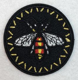 Zwart rondje met een rood en geel insect met witte vleugels applicatie