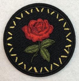 Zwart rondje met rode roos met olijfgroene bladeren applicatie