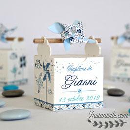 """Boite à dragées baguette en bois """"moulins à vent et nuages en liberty bleu"""" : petites fleurs en nuances de bleu clair à bleu marine avec feuillage en beige et gris"""