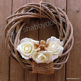 Türkranz aus Rattan mit Engel in gold dekoriert. Mit Jute und weißen Rosen.