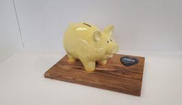 Sparschwein auf Holzbrett mit Glücks Schiefer
