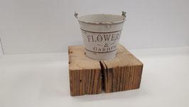 Blumentopf auf einem Altholzsockel