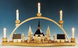 Schwibbogen mit beleuchteter Kirche und Häusern