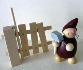 Wicht mit Hammer und Nägeln am Zaun