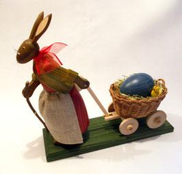 Osterhasengroßmutter mit Ei und Küken im Wagen