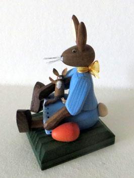 Hasenmädchen, sitzend mit Puppe