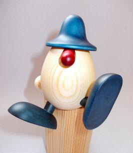 Eierkopf Alfons auf Kante sitzend, tanzend