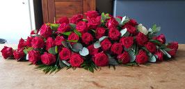 Langwerpig rouwarrangement met rode rozen