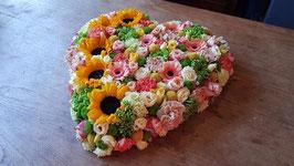 rouwhart 50 cm. opgemaakt in zachte tinten waar aan de rand zonnebloemen in zijn verwerkt