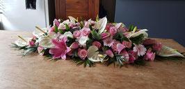 Langwerpig Rouwarrangement met anthuriums, lelies, rozen en gerbera's, lengte 110 cm.