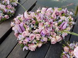 Dubbel open hart opgemaakt met anthuriums, rozen, clematis in lila tinten