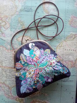 Bolso con cierre metálico con apliques de hojas y bordados