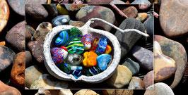 Kunstkarte Naturschale voller Glasherzen auf Steinen