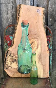 grüne Flasche auf schwerem Akazienbrett