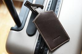 Praktische schlichte Kofferanhänger aus Leder in Stoffbeutel verpackt