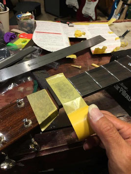 ギターネックの指板に黄色いマスキングテープを貼っている作業