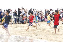 テープカット後、海に向かって駆け出す子ども達=19日午後、南ぬ浜ビーチ