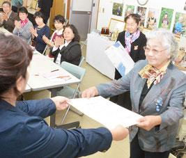 池村隊長から感謝状を受ける初代隊長の高西さん(右)。あいさつでは感謝の涙を流した=12日、沖縄県農林水産振興センター