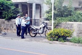 死亡した松川さんのバイクを調べる八重山署の捜査員=16日午後、産業道路周辺