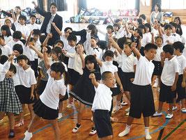 「ゆめのつばさ」の歌に合わせてこぶしを上げる児童=7日、八島小学校