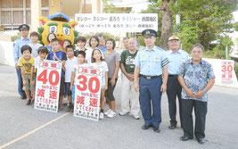 看板設置後に記念写真に収まる関係者ら=15日午後、川平小中学校正門前