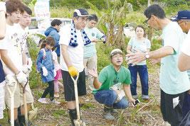 地元農家からサトウキビの捕植について説明を受ける法政大生ら=5日午後、崎枝公民館