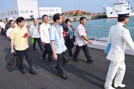 式典参加者たちが渡り初めを行った=16日、浜崎桟橋