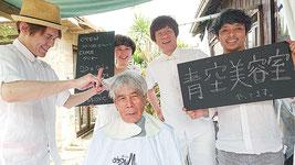 髪を切ってもらう花城新栄さんと、右から山口宏一郎さん、村瀬隆浩さん、山口奈緒美さん、坂井忍さん=20日、竹富島「ちいさな島宿cago」