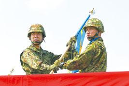 陸上自衛隊の小川清史西部方面総監(左)から隊旗を受け取る沿岸監視隊の塩満大吾隊長=28日午前、与那国町
