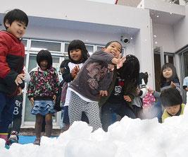 雪のプレゼントに大興奮の園児。雪合戦がスタートした=25日、みやら保育園