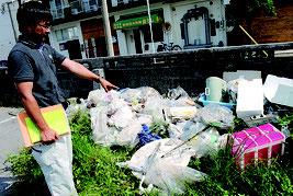 美崎町の企業有地に不法投棄されたごみを調べる市職員=12日午後