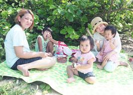 青い海を見ながら食事を楽しむ髙島さん親子=9日、名蔵海岸