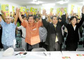 次呂久氏の出馬表明会見後、ガンバロー三唱で気勢を上げる次呂久氏(右から2人目)と支援者=29日午後、後援会事務所