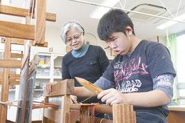 ミンサー織りを体験する生徒と講師を務めた大浜公江さん