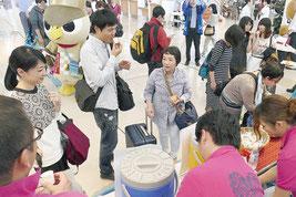 さんぴん茶やマンゴージュース、ちんすこうを楽しむ観光客ら=7日午後、南ぬ島石垣空港ターミナル